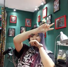 Female customer with dyed hair showing new tattoo on the forearm and giving the V sign