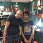 Male customer showing off his just completed arm tattoo with a female customer