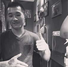 Male customer showing off tattoo on his hand and giving a thumbs up