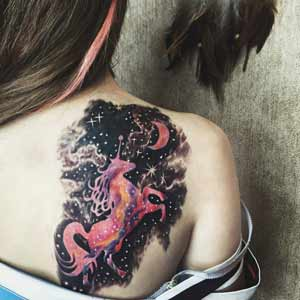 Woman's tattoo of a unicorn and crescent moon on right shoulder blade small