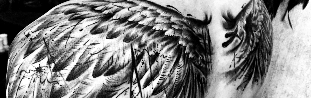 Tattoo of wings on shoulder blades